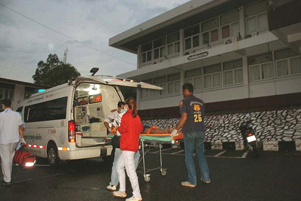 The father of an 8-year-old girl who was raped and subsequently died is loaded in an ambulance for transport to Trang Hospital