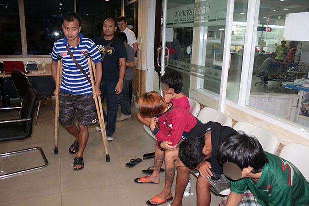 """Yotsapon """"James"""" Surawichai, 33, on crutches, looks at four underage boys he allegedly procured for male foreigners in Pattaya (Photo by Chaiyot Phuttanapong)"""