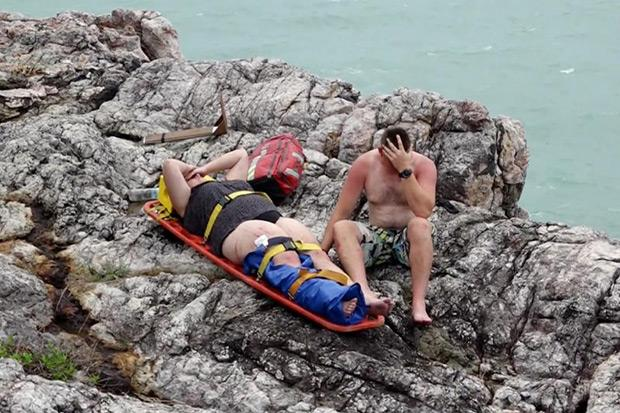 Rescued tourists rest on the shore after their boat capsized near Koh Samui.