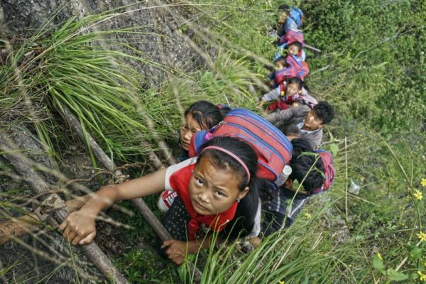 Children wearing their school backpacks climb on a cliff using a bamboo ladder on their way home from school in Zhaojue county, southwest China's Sichuan province