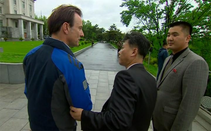 Rupert Wingfield-Hayes being led away from the entrance of Kim Il-sung University during a report.