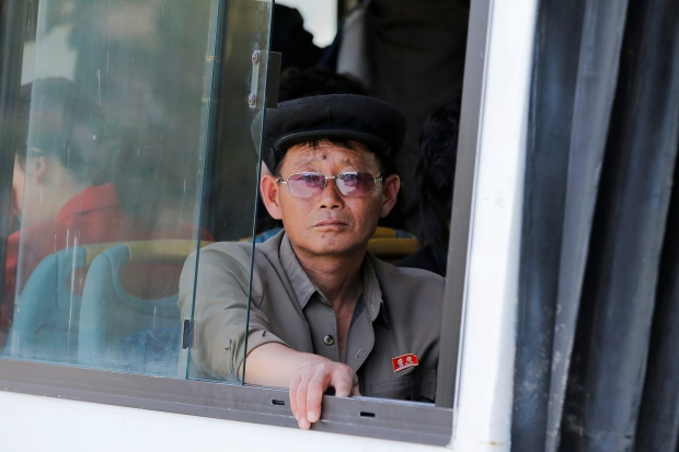 The only glimpse reporters have been able to get of average North Koreans has been through bus windows on their way from one scheduled tour to another. Photo - Damir Sagolj