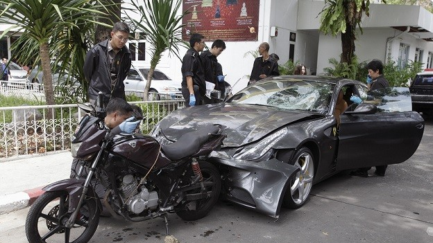 Police inspect a motorcycle belonging to Pol Snr Sgt Maj Wichian Klanprasert of Thong Lor police station and a Ferrari driven by Vorayuth Yoovidhya, the youngest son of Red Bull executive Chalerm