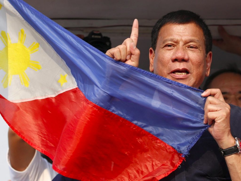 "Presidential elect Rodrigo ""Digong"" Duterte holds the national flag of the Philippines."