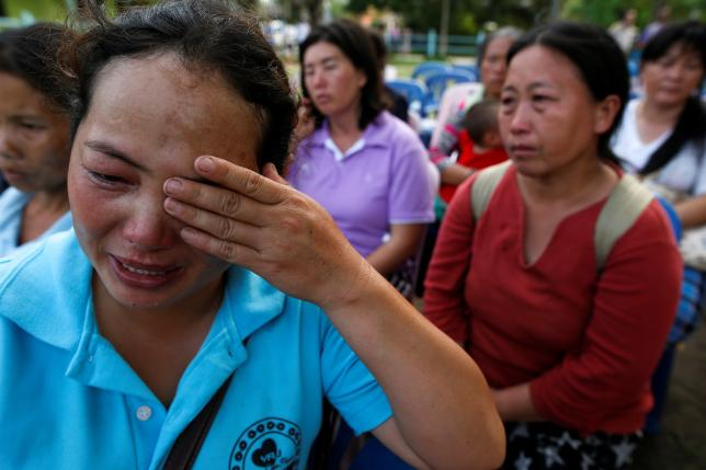 Malawian Saw-wa, 33, (L) who lost her daughter, cries near a burnt building at the Pitakkiat Wittaya School in the northern province of Chiang Rai, Thailand, May 23, 2016. Phtot Athit Perawongmetha