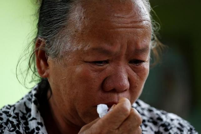 Na-me Pratikili, 57, who lost six relatives, weeps near a burnt building at the Pitakkiat Wittaya School in the northern province of Chiang Rai, Thailand, May 23, 2016. REUTERS/Athit Perawongmetha