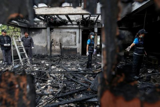 Forensic exports inspect a burnt building at the Pitakkiat Wittaya School in the northern province of Chiang Rai, Thailand, May 23, 2016. REUTERS/Athit Perawongmetha