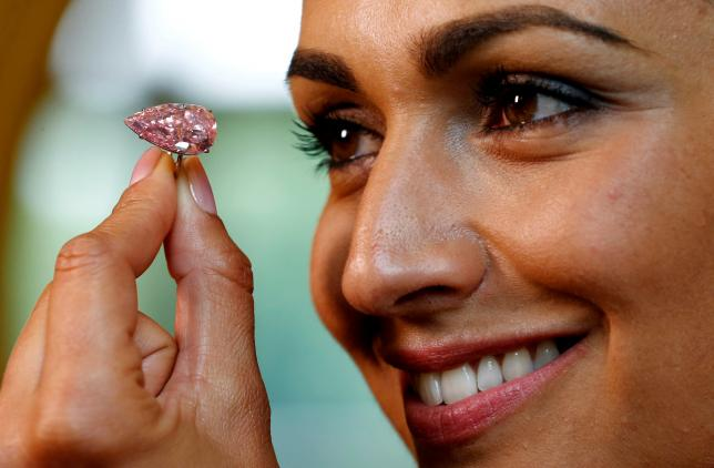 "A model poses with the ""Unique Pink"", a 15.38 carats vivid pink diamond, at Sotheby's auction house in Geneva, Switzerland May 9, 2016. REUTERS/Denis Balibouse/File Photo"