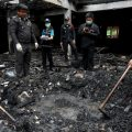 Forensic experts inspect a burnt building at the Pitakkiat Wittaya School. Photo Athit Perawongmetha