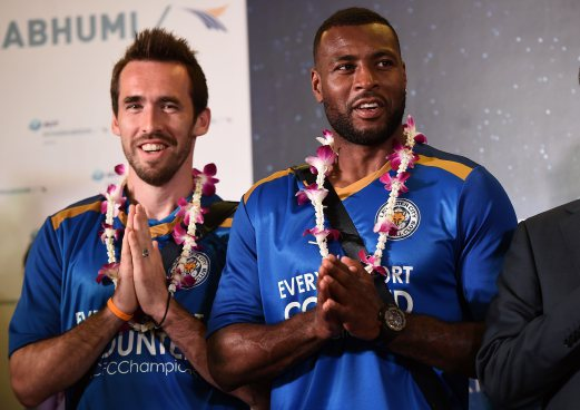 "Christian Fuchs and Wes Morgan greet the press with a traditional Thai ""wai"" gesture as Leicester City FC players arrive at Suvarnabhumi Airport in Bangkok on May 18, 2016. / AFP PHOTO / LILLIAN SUWANRUMPHA"