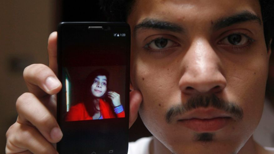 Hassan Khan shows the picture of his wife Zeenat Rafiq, who was burned alive, allegedly by her mother, on a mobile phone at his home in Lahore, Pakistan. (AP)