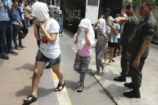 Female migrant suspects detained in Tuesday's raid at Nataree massage parlour on Ratchadaphisek Road in Bangkok cover their faces while walking into the Criminal Court