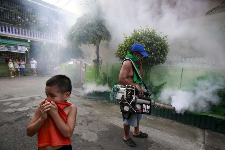 A boy covers his nose while a worker fumigates outside a residential area in Chiang Rai