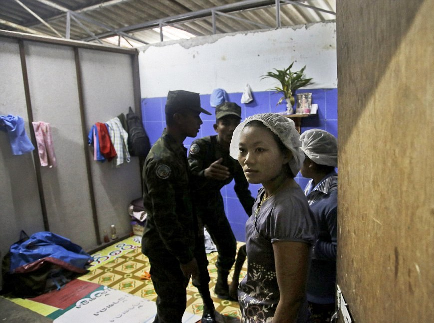 Thai soldiers search a room of the Myanmar workers living quarters during a raid.