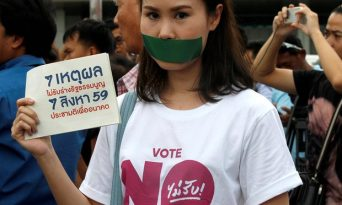 An activist against the junta-backed constitution seals her mouth with duct tape. Seven activists were jailed on Friday. Photograph: Chaiwat Subprasom/Reuters
