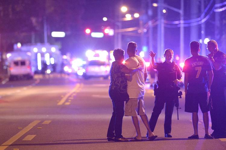 Orlando police officers direct family members away from a multiple shooting at a nightclub on Sunday