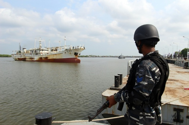An Indonesian Navy officer in April, standing before a Chinese trawler that was allegedly operating illegally