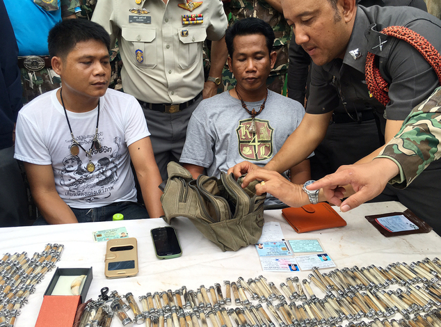 "A police officer, right, examines the belongings of two men arrested after attempting to remove tiger skin's and products from the ""Tiger Temple,"" in Saiyok district in Kanchanaburi province."