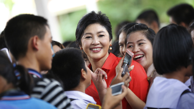 Students of Bueng Kan Wittaya school take photos with Thailand's former prime minister Yingluck Shinawatra in Bueng Kan Province, Thailand. As the former prime minister made her way through a line of fans, some cried, others screamed and a few embraced her. This was not a political campaign stop. If it had been, the generals who ousted Yingluck two years ago never would have let it happen. (AP Photo/Sakchai Lalit)