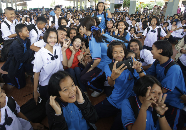 In this May 30, 2016 photo, students of Bueng Kan Wittaya school take photos with Thailand's former prime minister Yingluck Shinawatra at Bueng Kan Province, Thailand. As the former prime minister made her way through a line of fans, some cried, others screamed and a few embraced her. This was not a political campaign stop. If it had been, the generals who ousted Yingluck two years ago never would have let it happen. (AP Photo/Sakchai Lalit)