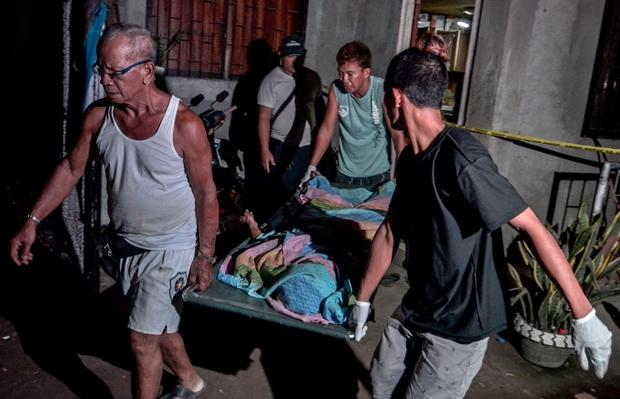 Officials carry out the dead body of one of four unidentified suspects killed during a shootout with suspected drug dealers in Norzagaray, Bulacan, north of Manila on Thursday
