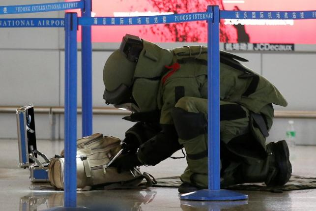 A bomb disposal expert checks a luggage near the site of a blast at a terminal in Shanghai's Pudong International Airport
