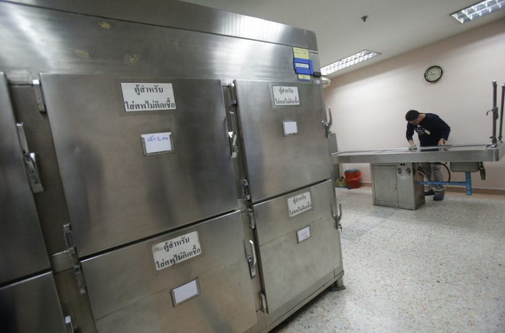 A Thai man convicted of drunk drinking cleans an autopsy table at Taksin Hospital in Bangkok