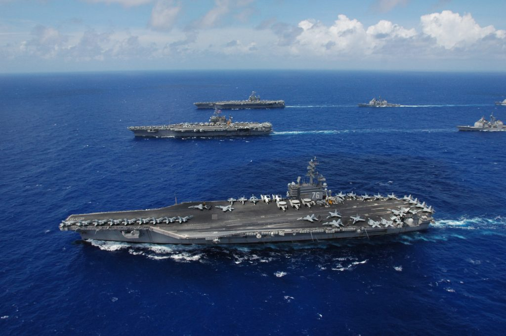 The Nimitz-class aircraft carrier USS Ronald Reagan, foreground, USS Kitty Hawk, center, USS Abraham Lincoln and their associated carrier strike groups steam in formation.