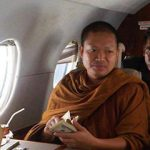 Phra Wirapol Sukphol aboard a private jet, brandishing a bundle of US dollar banknotes