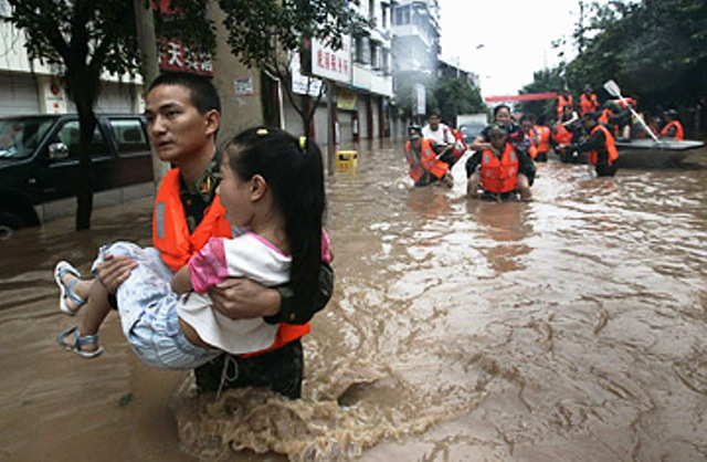 Paramilitary policemen helps a young girl to a safe area in Chongqing, China