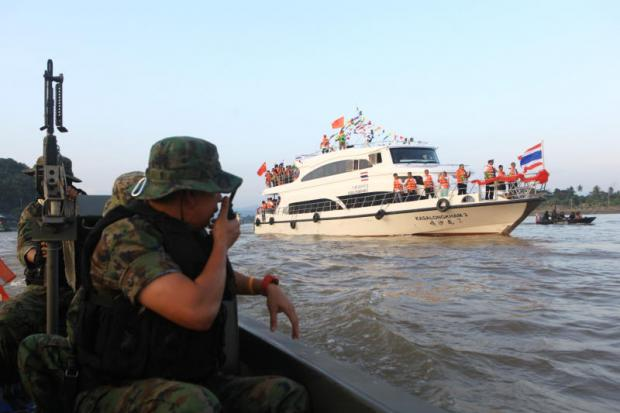 A military marine patrol provides security for the Thai-owned Kasalongkam II as it leaves Chiang Rai for southern China