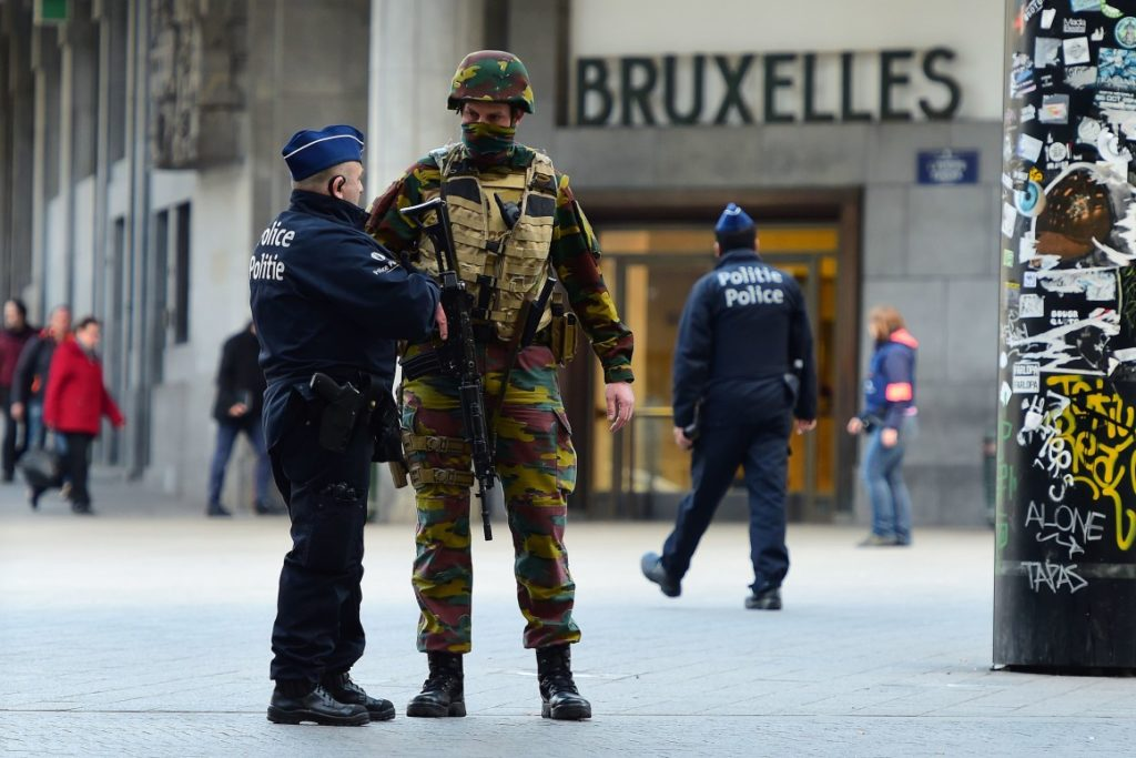 TOPSHOT - A Belgian soldier speaks to a police officer outside Brussels Central Station as people are allowed in small groups of ten to reach the station in order to take their commuter train following attacks in Brussels on March 22, 2016.  Airlines cancelled hundreds of flights and European railways froze links with Brussels after a series of bombs blasts killed around 35 people in the city's airport and a metro train, sparking a broad security response. / AFP / EMMANUEL DUNAND        (Photo credit should read EMMANUEL DUNAND/AFP/Getty Images)