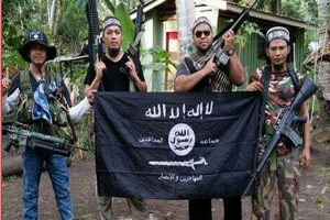 An Abu Sayyaf fighter with Malaysian militants Mahmud Ahmad, Muhammad Joraimee Awang Raimee and Muamar Gadafi, posing with an ISIS flag