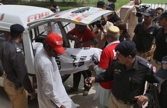 Pakistani police officers stand beside volunteers unloading the dead body of fashion model Qandeel Baloch upon arrival at a local hospital in Multan, Pakistan, July 16, 2016.