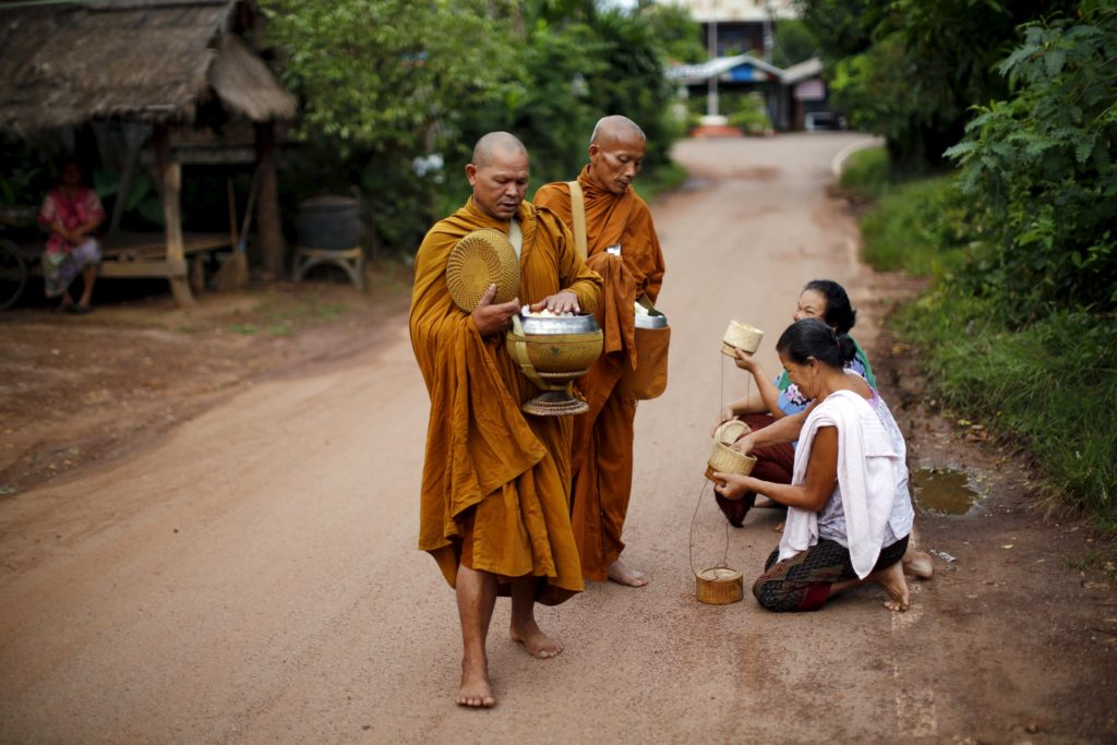 Buddhist monks receive rice from women early morning in a village outside Chiang Rai, Thailand.