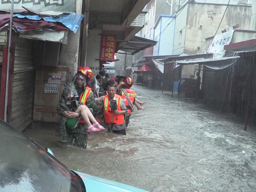 Firefighters evacuate residents stranded in flood to safety in Xiaogan, Central China's Hubei province, on Sunday. [Photo provided to China Daily]