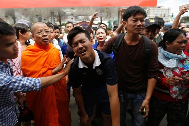 People comfort a relative of Kem Ley, anti-government figure and the head of a grassroots advocacy group, 'Khmer for Khmer' outside a gas station after he was shot dead in Phnom Penh