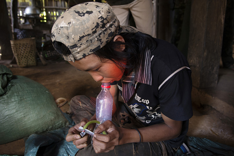A drug addict smokes a yabaa tablet (a name from Thai language for methamphetamine) in a Palaung area village. The whole Palaung area is plagued by the scourge of addiction to drugs such as opium, heroin and yabaa (methamphetamine).