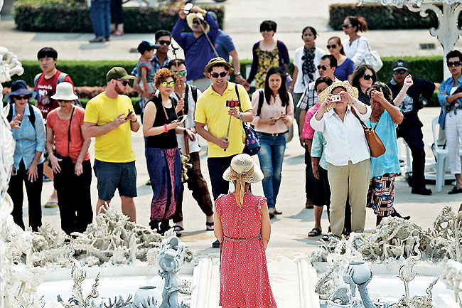 Chinese tourist posing for pictures as she visits Wat Rong Khun the White Temple in Chiang Rai.