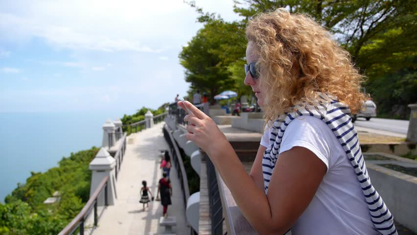 Young Woman with Mobile Phone near the Sea. View Point on Koh Samui. Thailand