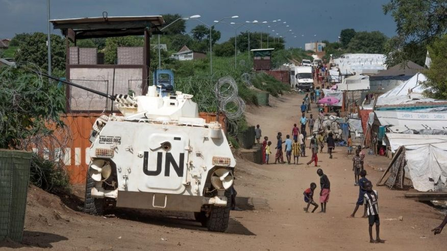Civilians sheltered in a United Nations base in South Sudan's capital Juba for fear of targeted killings by government forces walk by an armored vehicle and a watchtower manned by Chinese UN peacekeepers