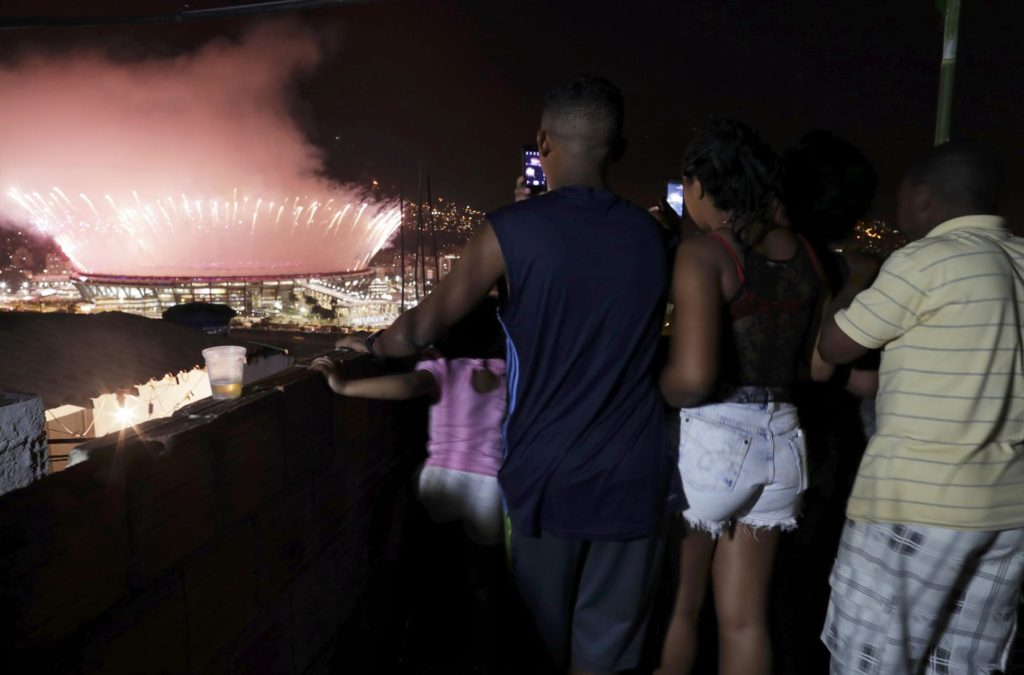 A family photographed fireworks over the Maracana stadium from the roof of their home in the Mangueira favela.