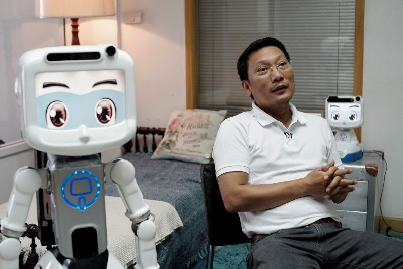CEO of CT Asia Robotics Chalermpon Punnotok and his Dinsow robot. Photo: Athit Perawongmetha/ Reuters