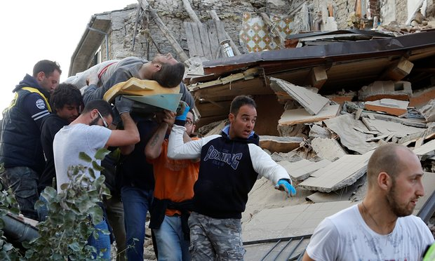 A man is carried away after having been rescued in Amatrice.