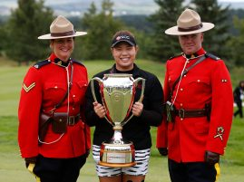 Ariya Jutanugarn of Thailand holds the Canadian Pacific Women's Open trophy with two members of the Royal Canadian Mounted Police.