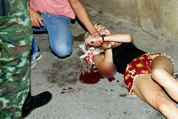 A girl receives first aid as she lies in a pool of blood on the street