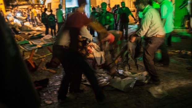 People carry an injured man on the site of the explosion in Gaziantep