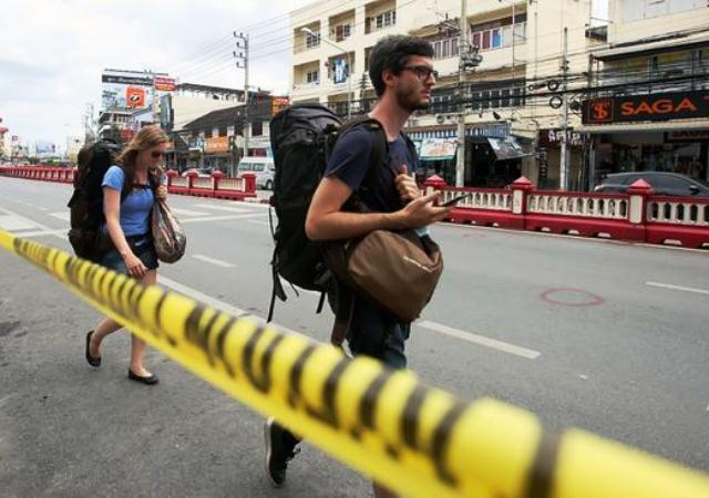 Tourists walk the scene of a bomb blast in the resort city of Hua Hin, Thailand, on Aug. 12, 2016. (EPA)