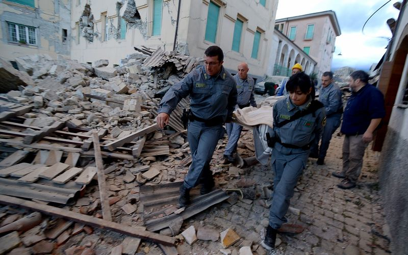 Rescuers carry a man from the rubble after a strong heartquake hit Amatrice on August 24, 2016.