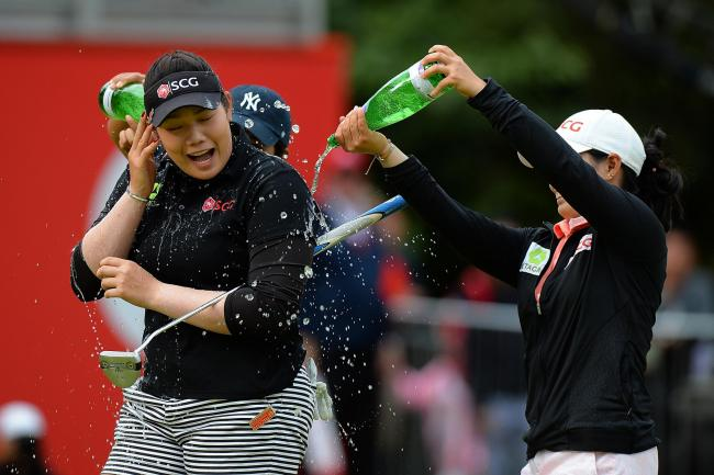 This is how you do it sis... Ariya Jutanugarn of Thailand gets a soaking from older sister Moriya after holing the winning putt at the RICOH Women's British Open - Photo by Tony Marshall